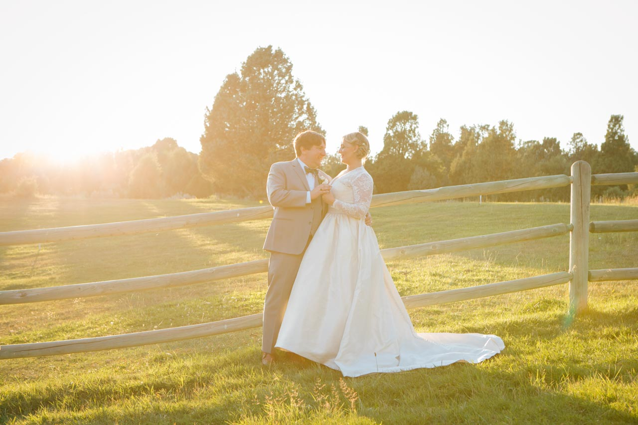 Couple portrait at sunset near rustic fence.