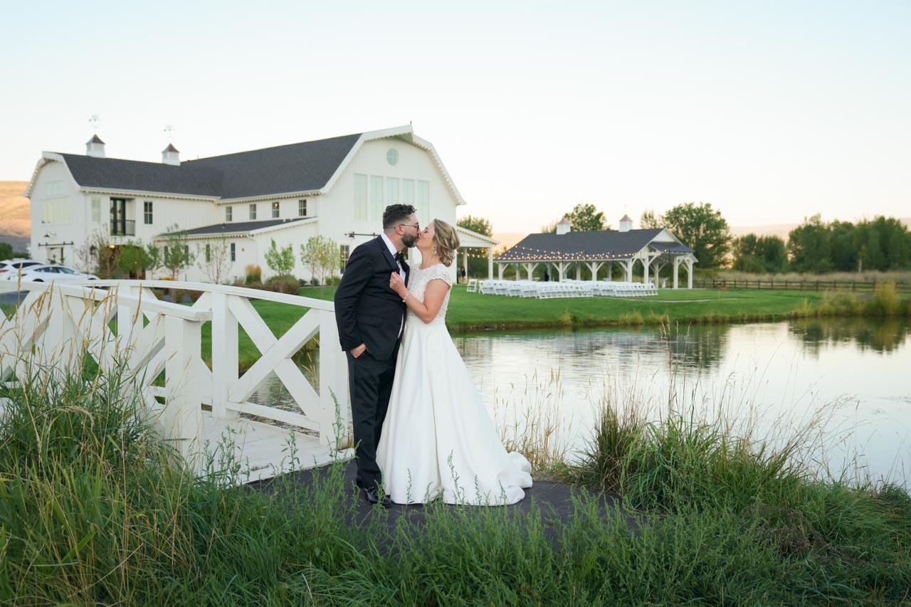 Newlyweds kiss outside River Bottoms Ranch at dusk.