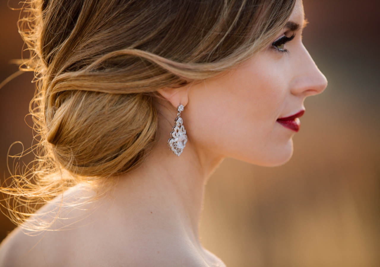 Wedding hair and makeup with warm tones and red lips.