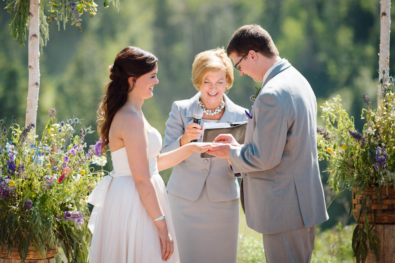 Wedding officiant smiles as the couple exchange rings.