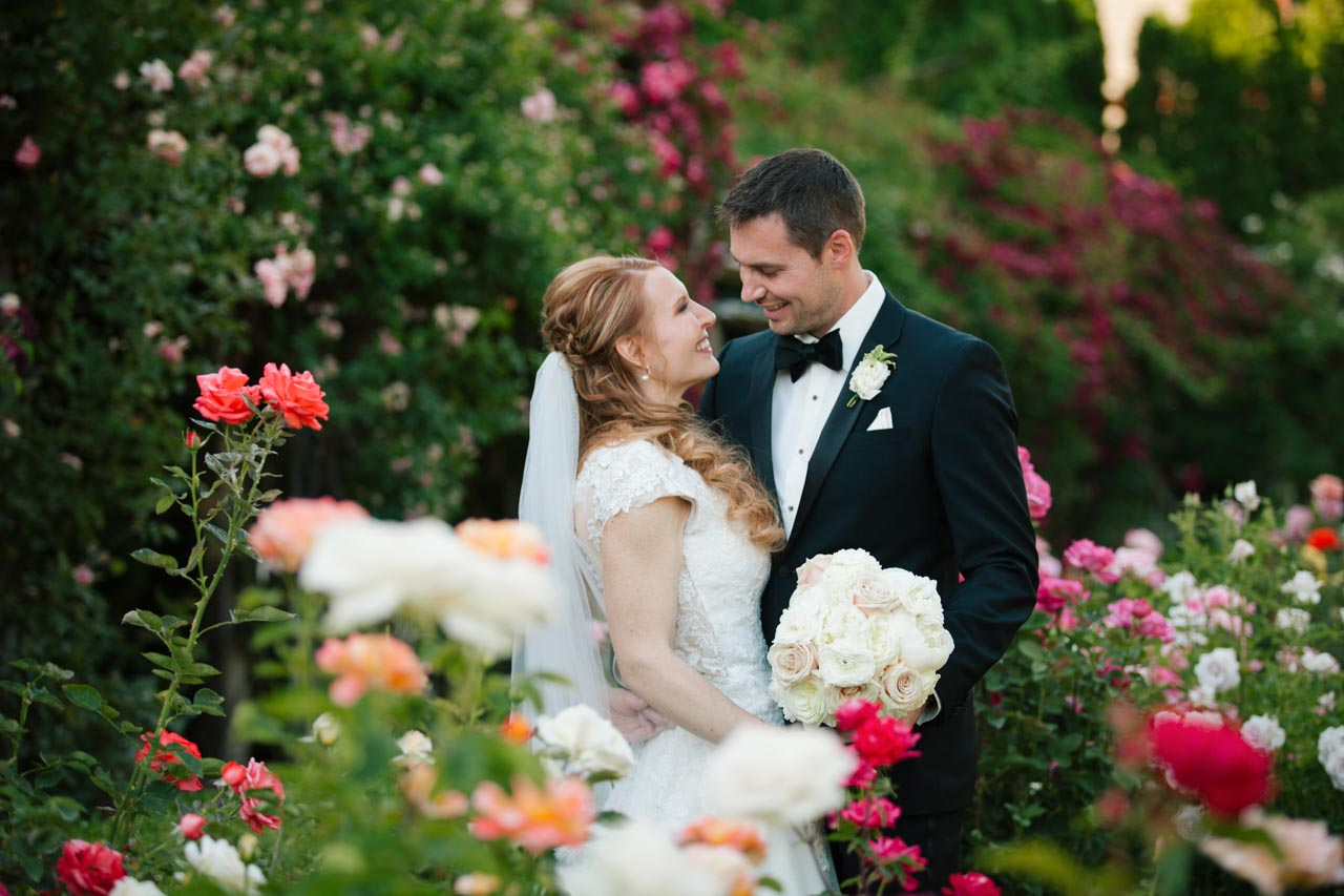 Newlywed couple in rose garden at Thanksgiving Point.