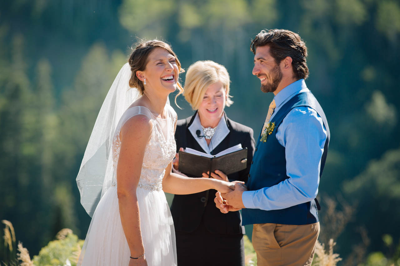 Bride laughs during ring exchange at her Alpine Meadows ceremony.