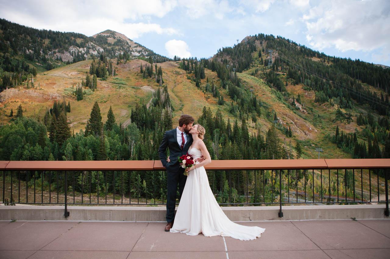 Couple kisses amid breathtaking fall mountains at Snowbird's Aerie.